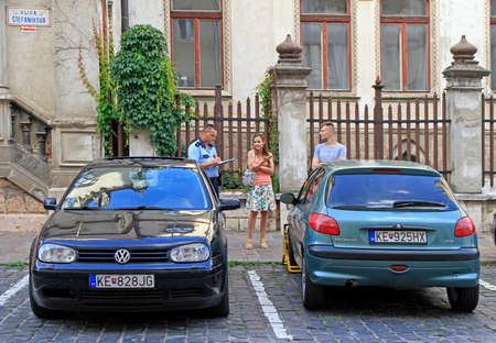 Kosice, Slovakia - June 28, 2017: officer of traffic police is registring the breaking of rules of parking in Kosice, Slovakia