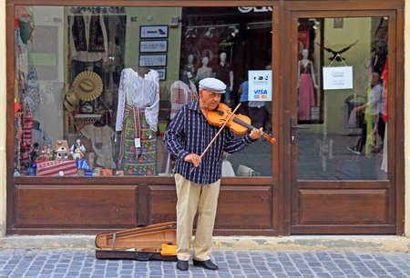 Brasov, Romania - July 25, 2017: street musician is playing violin outdoor in Brasov, Romania