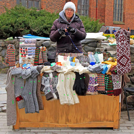 woman is selling souvenirs and warm clothes outdoor in Riga, Latvia Standard-Bild - 111543072