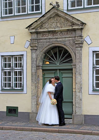 Riga, Latvia - April 29, 2017: fiance and bride are kissing at the entrance of one of buildings of landmark 'Three Brothers' in the old city of Riga, Latvia Éditoriale