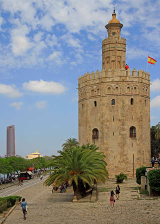 people are walking at golden tower in Seville, Spain