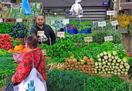 Tel Aviv, Israel - November 30, 2017: man sells greens at Carmel market in Tel Aviv, Israel