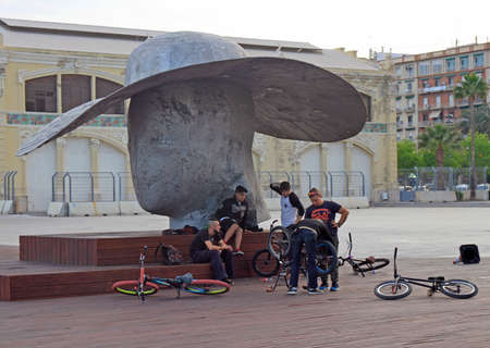 Valencia, Spain - April 24, 2018: adolescents are hunging out at sculpture 'The Pamela Hat' by spanish artist Manolo Valdes in city Valencia, Spain. this photo was made in open place with the free access for everyone