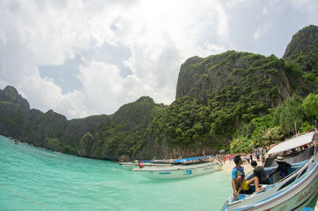 KRABI, THAILAND - April 28, 2017: Holidaymakers relaxing on the beach in Railay Beach. This is a popular tourist destination. Image contain certain grain or noise and soft focus.