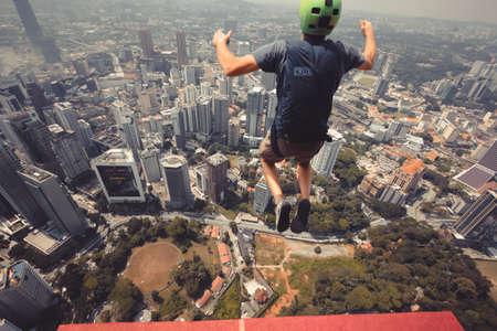 Kuala Lumpur, Malaysia – September 28, 2018: Base Jumpers jump from a 300m high deck during the Kuala Lumpur Tower International Jump.