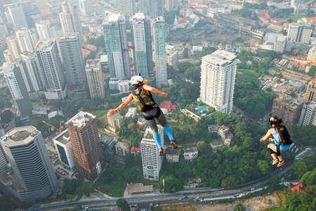 Kuala Lumpur, Malaysia – September 29, 2018: Base Jumpers jump from a 300m high deck during the Kuala Lumpur Tower International Jump.