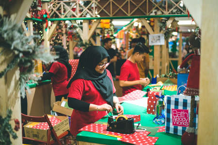 Kuala Lumpur, Malaysia - December 2020: Preparing for Christmas. Young Asian hands pack a gift