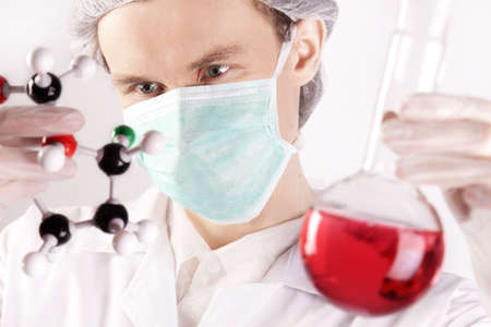 Scientist Holding Flask and Atoms photo