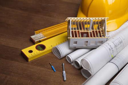 Piani di costruzione con il casco e gli strumenti di disegno su progetti