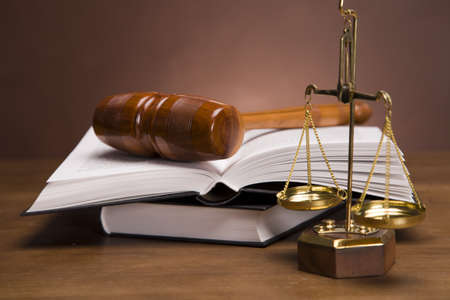 Bilancia della giustizia e martello sulla scrivania con sfondo scuro Archivio Fotografico