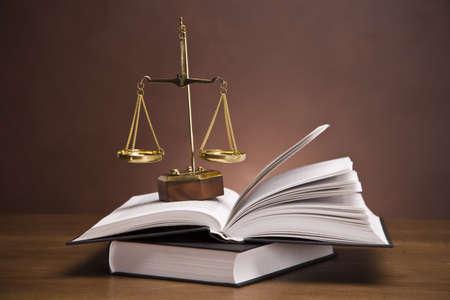 Waage der Gerechtigkeit und Hammer auf Schreibtisch mit dunklem Hintergrund