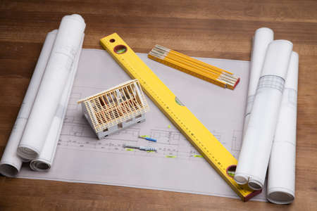 Construction plans and blueprints on wooden table photo