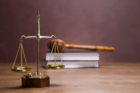 balanza de la justicia: Las escalas de la justicia y martillo en el escritorio con fondo oscuro Foto de archivo