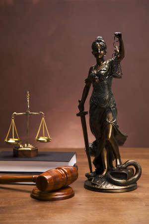 derecho penal: Balanza de la justicia y el martillo en el escritorio con fondo oscuro
