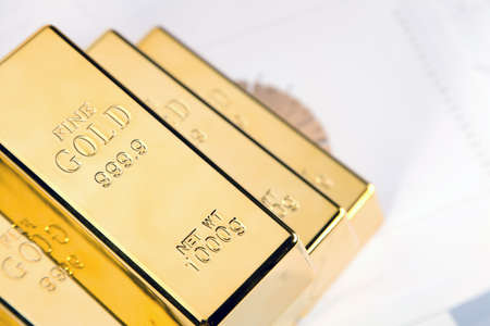 Photo of gold bars on graphs and statistics, studio shots, closeup photo