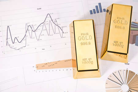 Photo of gold bars on graphs and statistics, studio shots, closeup Foto de archivo