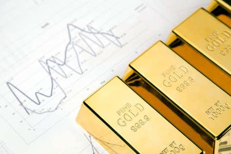 precious metal: Photo of gold bars on graphs and statistics, studio shots, closeup Stock Photo