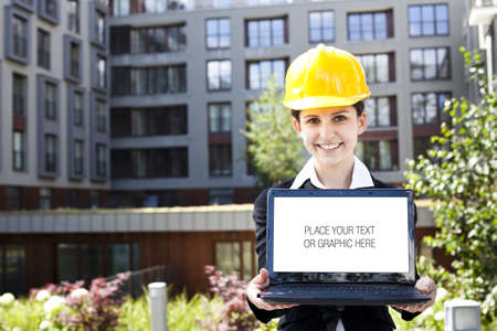 Female construction engineer show something on laptop photo