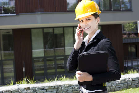 Young female construction engineer with phone photo