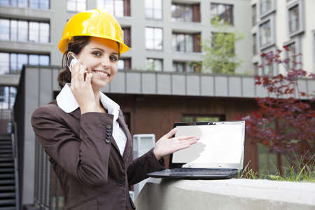 Female construction engineer show something on laptop Stock Photo - 14587640
