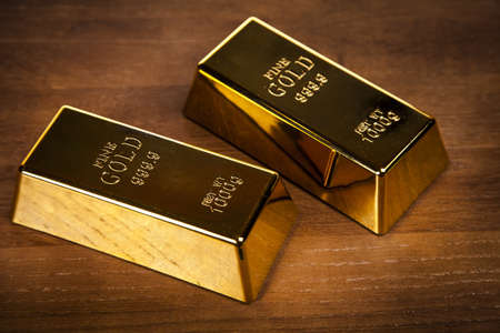 Two gold bars on wooden table  photo
