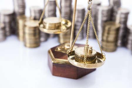 balanza en equilibrio: Una gran cantidad de monedas de dinero en escalas Foto de archivo