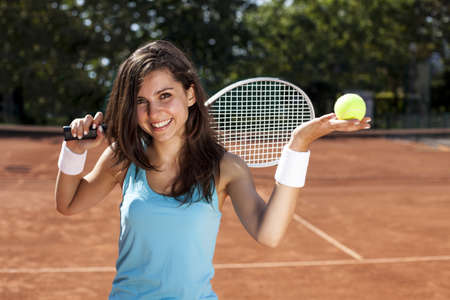 Young girl holding tennis ball on red court Stockfoto