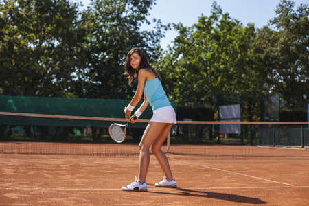 Young pretty girl playing tennis at the beautiful weather photo