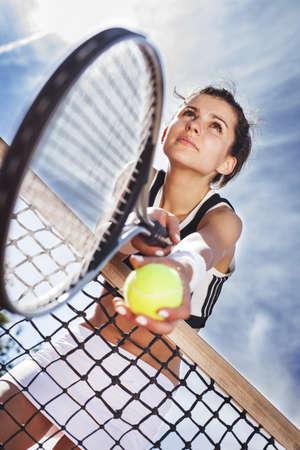 아름 다운 젊은 여자는 하늘에 테니스 그물에 달려있다