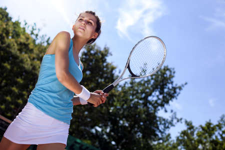 Toung pretty girl playing tennis at the beautiful weather photo