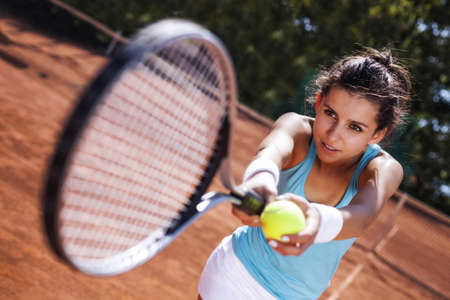 Young girl catching a ball in tennis court in pretty day photo