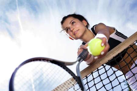 jugando tenis: hermosa joven se apoya en una red de tenis en el cielo Foto de archivo