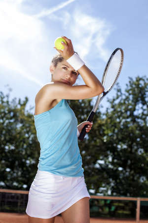 Young girl holding tennis ball on red court photo