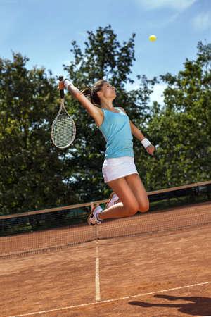 jugando tenis: Chica joven que juega al tenis en la cancha en un hermoso día soleado
