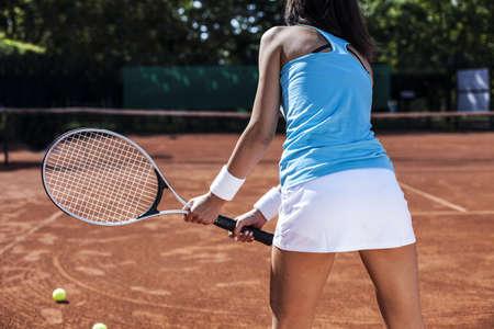 jugando tenis: Muchacha que juega a tenis en la pista en un hermoso día soleado Foto de archivo