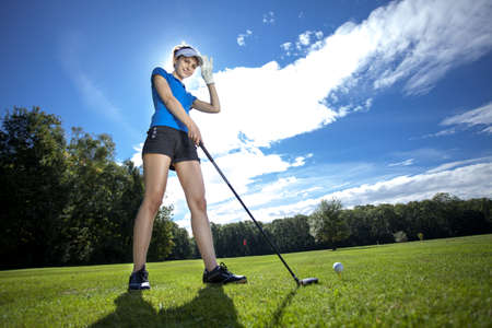 Pretty Woman playing golf on field Stock Photo - 22153030