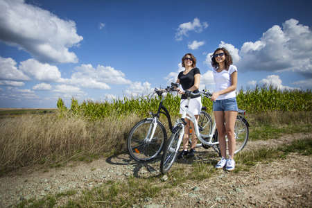 Two pretty girls on bike tour on rock path photo