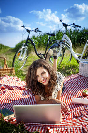 Women, picnic and computer  On grass in summer photo