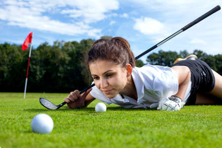 putter: Pretty girl playing golf on grass in summer