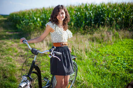 Pretty girl with bike on grass photo