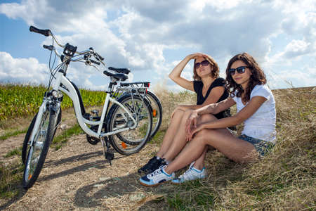 young womens: Two pretty girls on bike tour on rock path Stock Photo