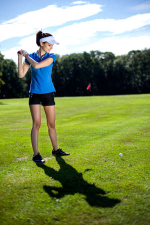 Pretty girl playing golf on grass in summer photo
