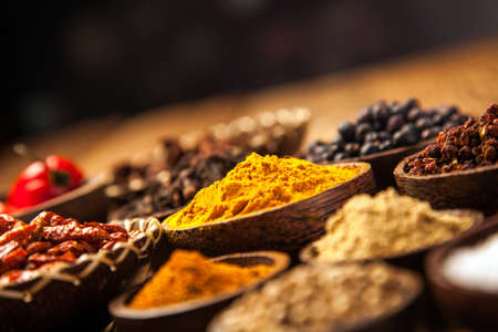 A selection of various colorful spices on a wooden table in bowls Stockfoto