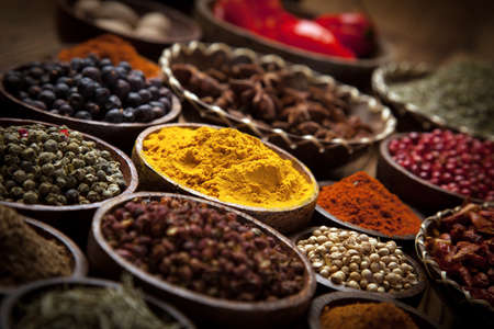 A selection of various colorful spices on a wooden table in bowls Stock Photo