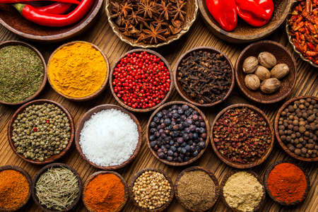 A selection of various colorful spices on a wooden table in bowls Foto de archivo
