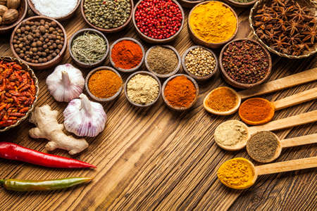 A selection of various colorful spices on a wooden table in bowls Stock fotó
