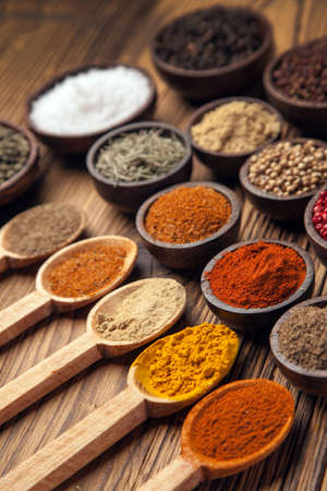 A selection of various colorful spices on a wooden table in bowls photo