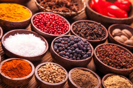 indian spices: A selection of various colorful spices on a wooden table in bowls Stock Photo