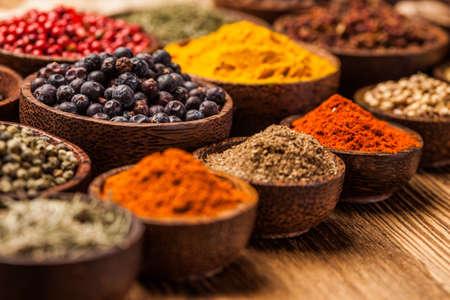 Een selectie van verschillende kleurrijke kruiden op een houten tafel in kommen