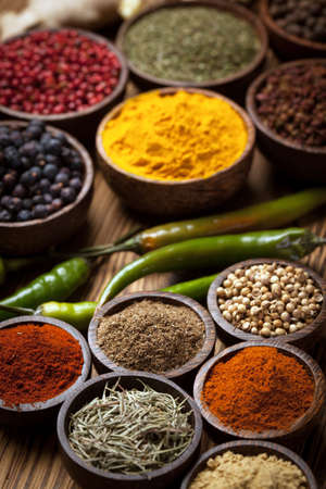 A selection of various colorful spices on a wooden table in bowls Фото со стока - 24434345